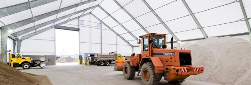 Camiones barre nieves cargan en un edificio de almacenamiento de sal