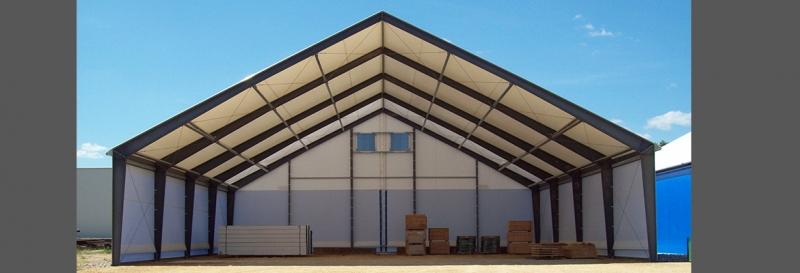 Tensoestructura para almacenes con paredes descubiertas a los extremos y con un panel de tipo malla para ventilacion