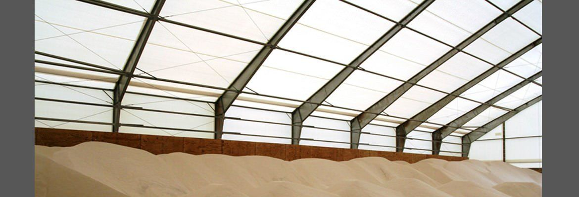 Tension fabric structure with peak exhaust vents for storing commodities.